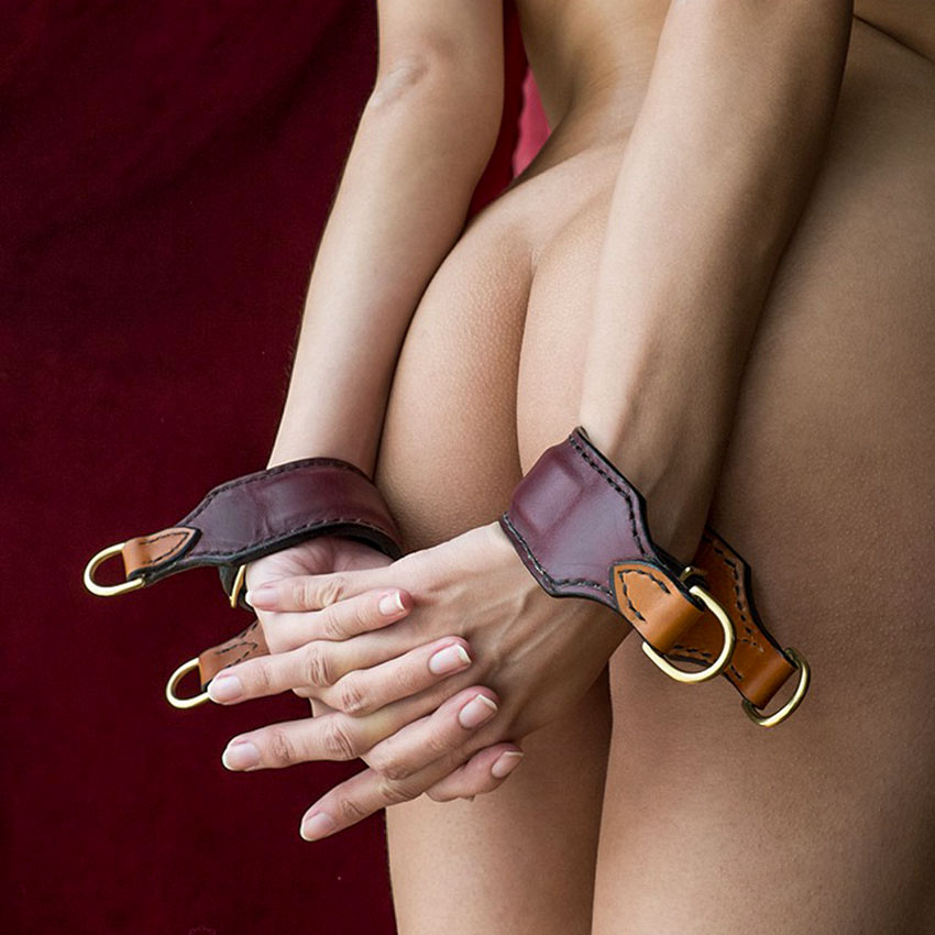 A nude girl wearing a handmade Premium Leather Wrist Cuff Pair by Paraphilia. Exclusive bondage restraints from the stockroom.